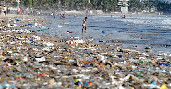 young boy and garbage strewn beach